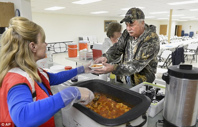 Help: A volunteer dishes a plate a Illinois resident at a shelter set up at River's Edge United Methodist Church in Spring Bay, Ill.