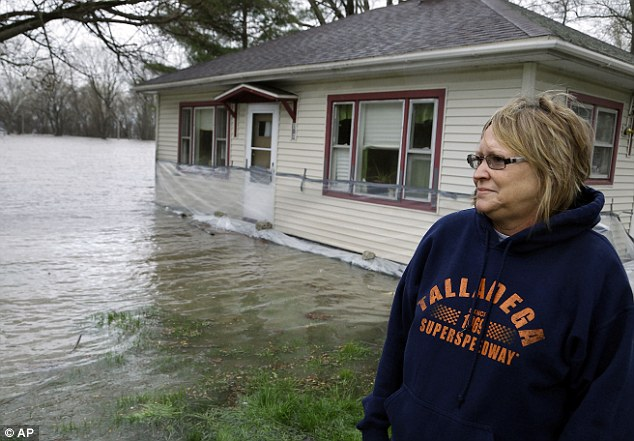 Disbelief: Jeanette Bricker watches the Illinois River rises out of it's banks surrounding and flooding her home