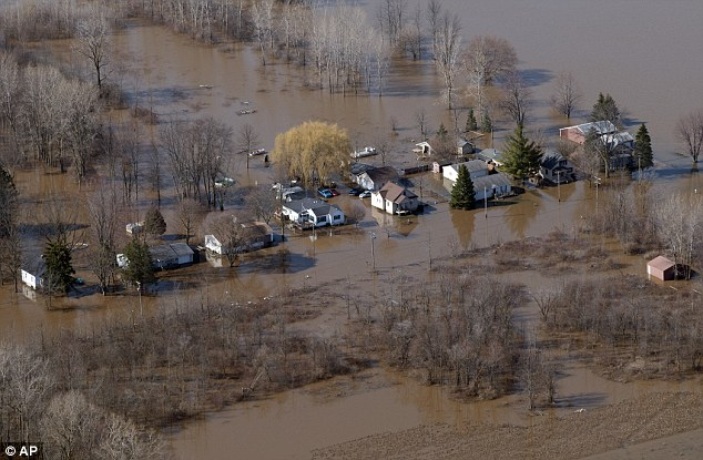 Homes along West Michigan near the Tittabawassee River in Saginaw Township are flooded on Monday