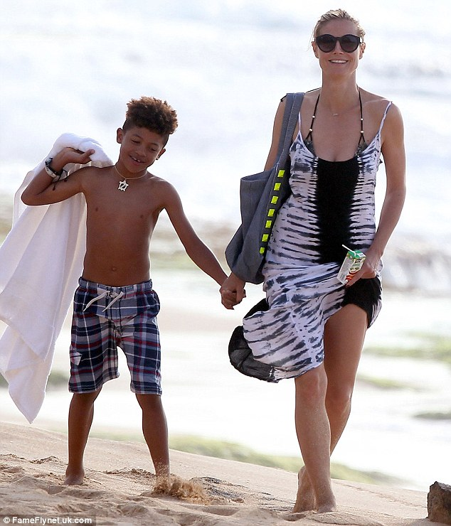 Hand in hand: Heidi is pictured walking along the sand with her son Henry on Tuesday last week