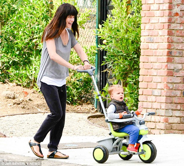 Having fun: The 40-year-old looked to be having fun as she gave her son a helping hand on his tricycle