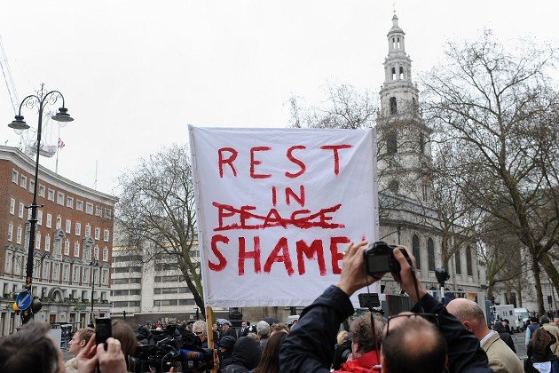 Phil Williams from Chester holds a banner outside the Courts of Justice in the Strand prior to the funeral service of Baroness Thatcher