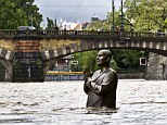 A statue is partially submerged by the rising waters of the Vltava River in Prague