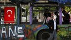 An anti-government protester wearing a Guy Fawkes mask walks past a burnt public bus used as a barricade