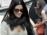 Sandra Bullock takes her son Louis Bardo to school this morning and looked great in an olive V-neck sweater