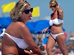 Bikini-clad Kim Zolciak continues to keep mum on pregnancy rumours as she puffs on another cigarette at the beach