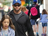 Doting dad: Hugh Jackman carried his daughter Ava's pink backpack during their stroll in NYC's West Village on Wednesday