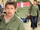 Sending a message? Busy Ethan Hawke reads The Return Of The Prodigal Son as he arrives home in LA