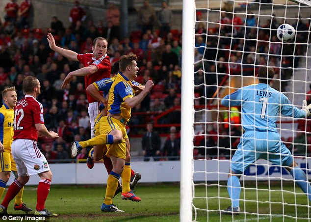 Rising above: Artell leaps to head in Wrexham's opener on the stroke of half-time