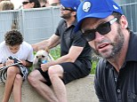 Actor Hugh Jackman helps his son with homework while out in a New York City park Saturday