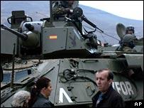 Pedestrians walk past a Nato military vehicle in Mitrovica (AP)