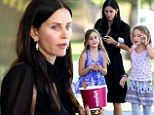 A sweet treat! Courteney Cox digs into a tub of frozen yoghurt on an outing with daughter Coco