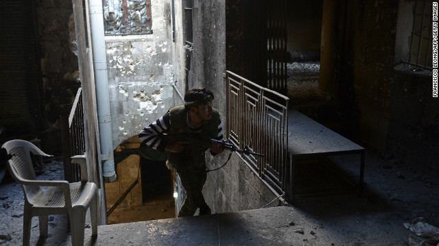 A Syrian rebel takes cover during fighting against Syrian government forces in Aleppo on November 15.