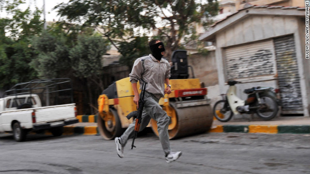 A Syrian rebel runs in a street of Selehattin during an attack on the municipal building on July 23.