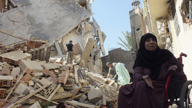 A woman sits in her wheelchair next to her house, damaged by a Syrian air raid, near Homs on August 26.