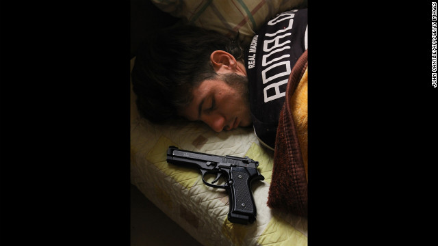 Syrian opposition fighter Bazel Araj, 19, sleeps next to his pistol in Aleppo on November 11.