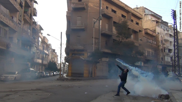 A protester in Homs throws a tear gas bomb back towards security forces, on December 27, 2011.