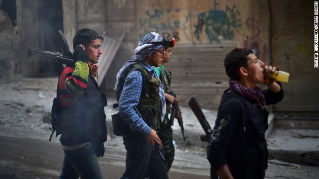 Syrian and Kurdish rebel fighters walk in the Sheikh Maqsud district of Aleppo on April 14.