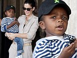 Intrepid traveller! Sandra Bullock cradles her stylish toddler Louis as she prepares to depart Germany