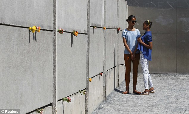 Close bond: The two sisters look deep in discussion as they leave flowers at the Holocaust memorial in Berlin on Tuesday