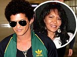 The show must go on: Bruno Mars puts on a brave face at airport following mother's tragic death as he prepares for world tour
