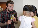 Toy boy: Beckham plays with a child suffering from congenital heart disease at a hospital in Hangzhou, Zhejiang province