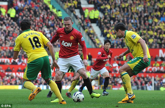 You're surrounded: Rooney tries to weave his way through a group of Norwich defenders