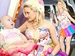 You're scaring me Mommy! Holly Madison overdoes it as the candy-coated fairy at carnival with baby Rainbow