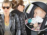 Gisele Bundchen pushes her daughter though the crowds at a Los Angeles airport after returning from European holiday