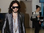 Keeping her distance! Russell Brand makes new lady friend walk several steps behind him as they jet into LA