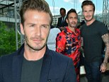 Try harder next time, David! Casual Becks is upstaged by Marc Jacobs as designer wears a colourful trouser suit at Paris Fashion Week