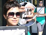 Kourtney Kardashian arrives at a frame store in Calabasas carrying some picture frames along with a roll of textured paper