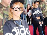 Rihanna rocks the geek look in thick-rimmed glasses and baseball cap as she greets fans in Cologne