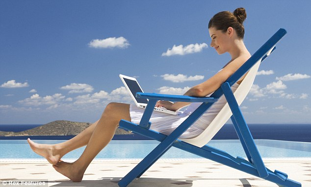 A woman on laptop on the beach