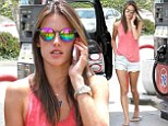Alessandra Ambrosio shows off her model figure in denim shorts as she pumps gas