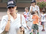 'Happy hour for me': Brooke Burke-Charvet dutifully swallows a wellness shot at a juice bar as her children chow down on ice cream