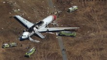 Crashed Asiana Airlines Boeing 777 aircraft surrounded by search and rescue officials
