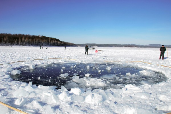 The Chelyabinsk meteorite punctured the ice of Chebarkul Lake near Chelyabinsk, Russia. Photograph from Asahi Shimbun/Getty Images.