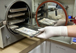 Technician Inserts Surgical Instruments in Autoclave for Sterili