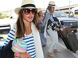 She's got wings! Angel Alessandra Ambrosio shows spirit in striped top and Panama hat as she hauls her luggage to LAX