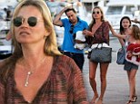 Kate Moss kicks off her flip flops and goes barefoot in long sleeved top and tiny shorts as she relaxes on holiday with husband Jamie and daughter Lila