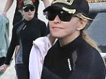 Sun shy Madonna carefully covers up in wetsuit, hat and sunglasses on eve of her 55th birthday as she enjoys a family outing on beach