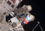 A cosmonaut unfurls a Russian flag outside the ISS during a spacewalk on Thursday to mark Russian Flag Day.