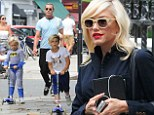 That's not summer-wear: Gwen Stefani covers up in a winter coat as her boys enjoy the London sunshine