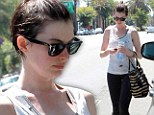 Holey smokes! A make-up free Anne Hathaway sweats it out in a ripped up tank at the gym