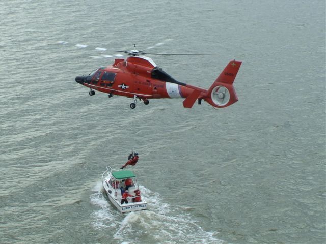 photo of rescue swimmer hoisted to or from USCG aux vessel lucky strike. taken from second helo at higher altitude.