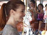 All the fun of the fair! Alyson Hannigan and daughter Satyana wear matching beaming smiles as they ride the carousel in Malibu