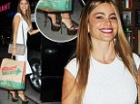 Modern Family's Sofia Vergara somehow stays upright in six inch stiletto platforms as she collects the family dinner