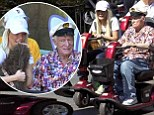 Well he is 87! Hugh Hefner zooms around Disneyland on a mobility scooter... and wife Crystal, 27, gets one too
