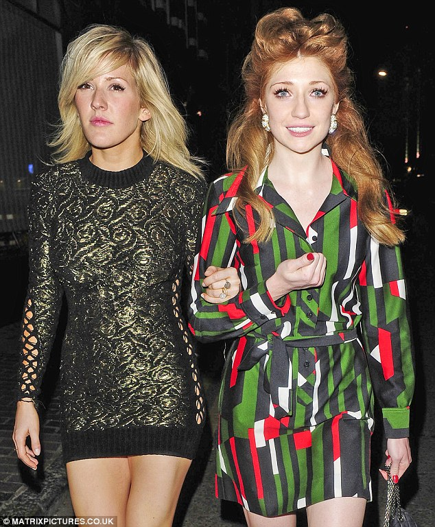 Legs on show: The girls looked like the best of friends as they linked arms and strutted along the streets